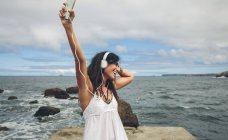 Mulher feliz em um cais ouvindo música com fones de ouvido — Fotografia de Stock