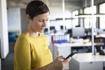 Femme d'affaires à l'aide de téléphone portable au bureau — Photo de stock