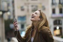 Giovane donna felice ascoltare musica con auricolari e smartphone — Foto stock