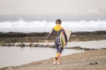 Spain, Tenerife, Boy walking on beach carrying surfboard — Stock Photo