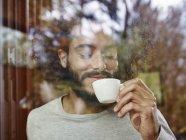 Giovane che gode della tazza di caffè dietro vetro sorridente — Foto stock