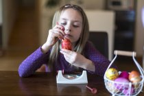 Girl painting Easter egg at home — Stock Photo