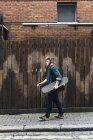 Jovem com skate andando na rua, em Dublin, Irlanda — Fotografia de Stock