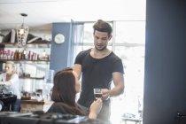 Женщина в парикмахерской получает чашку кофе — стоковое фото