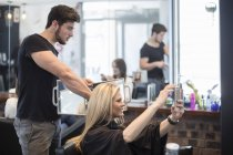 Woman in hair salon checking hairstyle in mirror an taking selfie — Stock Photo