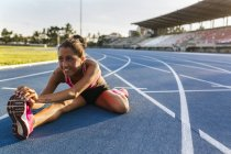 Gijn, Asturias, Spain, athlete woman doing stretching in a race track — Stock Photo