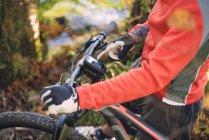Primer plano del ciclista de montaña utilizando el dispositivo gps de la bicicleta de montaña - foto de stock