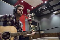 Человек, играть на гитаре в студии во время записи музыкального — стоковое фото