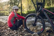 Mountain biker resting and smiling near river with mountain bike — Stock Photo
