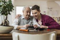 Senior man and grandson repairing toy train at home — Stock Photo