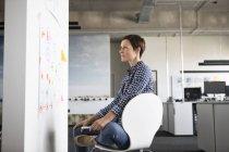 Geschäftsfrau, die Mind-Map im Büro zu betrachten — Stockfoto