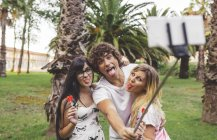 Playful friends in park taking a selfie using selfie stick — Stock Photo