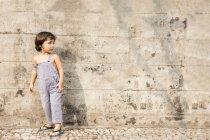 Ragazzino in piedi davanti al muro di cemento in estate — Foto stock