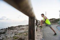 Pareggiatore che allunga il piedino sul recinto di legno in mare — Foto stock