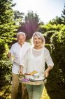 Elderly couple carrying carafe and tray in garden — Stock Photo