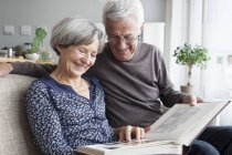 Happy senior couple sitting on the couch of living room watching photo album — Stock Photo