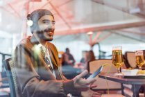 Smiling man with headphones and cell phone at outdoor bar — Stock Photo