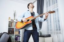 Young man at home playing guitar — Stock Photo