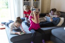 Five children on one couch using different digital devices — Stock Photo