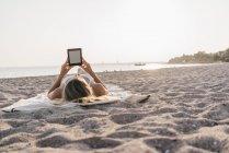 Молодая женщина, лежа на одеяло на пляже с помощью планшета — стоковое фото