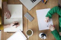 Zugeschnittenes Bild Frau schreiben in Notebook mit Sohn Zeichnung am Tisch — Stockfoto