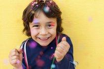 Feliz niño de pie frente a la pared amarilla mientras confeti cayendo sobre él - foto de stock