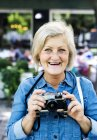 Cheerful senior adult woman holding camera outdoors — Stock Photo