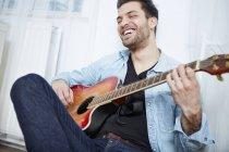 Glücklicher junger Mann, der Gitarre spielt — Stockfoto