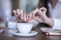 Человек, положить подсластитель в кофе — стоковое фото
