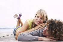 Smiling young couple lying on a jetty — Stock Photo