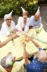 Group of seniors celebrating, drinking champagne at garden — Stock Photo