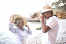 Active cute senior couple taking photo on camera at beach — Stock Photo