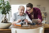 Senior man and grandson with toy train and mini tablet at home — Stock Photo
