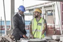 Construction worker and businessman discussing on construction site — Stock Photo