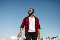 Sonriente hombre escuchando música con auriculares al aire libre - foto de stock