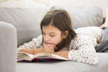 Ragazza sdraiata sul divano e leggere un libro — Foto stock