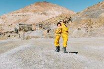 Bolivien, Potosi, zwei Touristen tragen Schutzkleidung stehen Rücken an Rücken vor Cerro Rico — Stockfoto