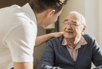 Ritratto di uomo anziano sorridente faccia a faccia con la sua infermiera geriatrica — Foto stock