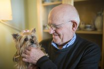 Senior man with his Yorkshire terrier at home — Stock Photo