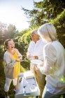 Heureux amis âgées debout avec des plats dans le jardin — Photo de stock