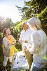 Happy elderly friends standing with dishes in garden — Stock Photo
