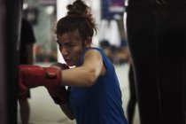 Female boxer exercising at punch bag — Stock Photo