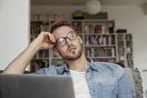 Портрет задумчивого человека с ноутбуком, сидящего в гостиной — стоковое фото
