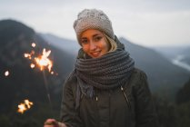 Portrait of smiling young woman holding sparkler outdoors — Stock Photo