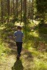 Rückansicht eines Jungen, der in den Wald geht — Stockfoto
