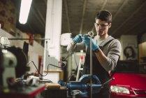 Молодой механик, работающих в ремонт гаража — стоковое фото