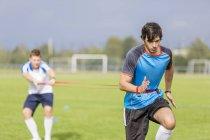 Deux joueurs de football faisant de l'exercice sur un terrain de sport — Photo de stock