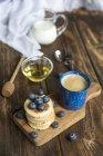 Stapel von Mini-Pfannkuchen, Heidelbeeren, Schale mit Honig, Milch und eine Tasse Kaffee — Stockfoto