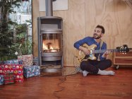 Man sitting on floor and playing electric guitar by Christmas tree — Stock Photo