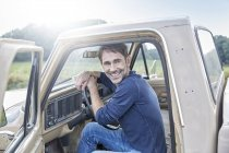 Smiling man sitting in van in nature — Stock Photo